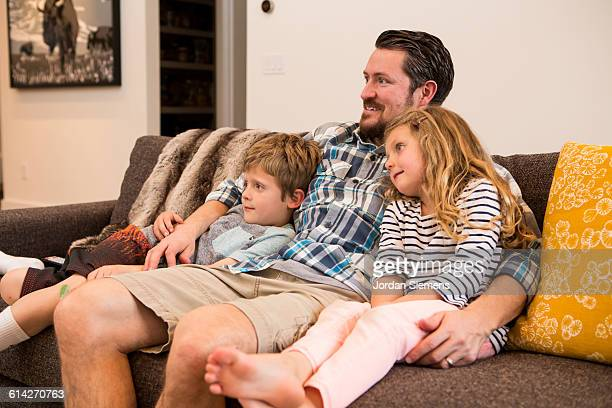 a dad watching a movie with his kids. - leanintogether stock pictures, royalty-free photos & images