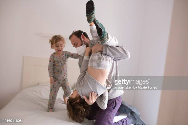 dad wearing surgical mask holding one son while the other watches - funny surgical mask stock pictures, royalty-free photos & images