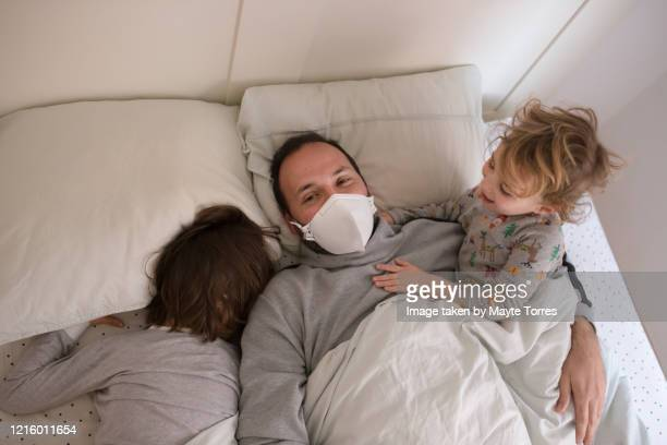 dad wearing surgical mask lying in bed with sons - real body fotografías e imágenes de stock