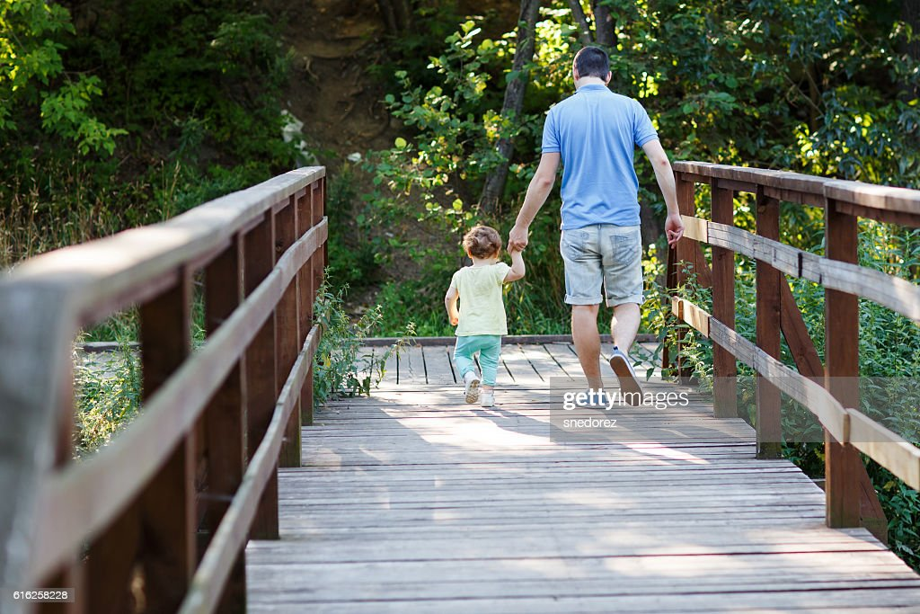 Dad with little daughter down wooden stairs in park : Foto de stock