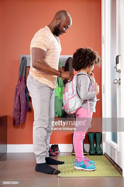 Dad zipping up daughter's backpack