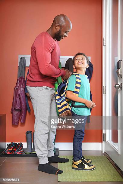 Dad zips up son's backpack