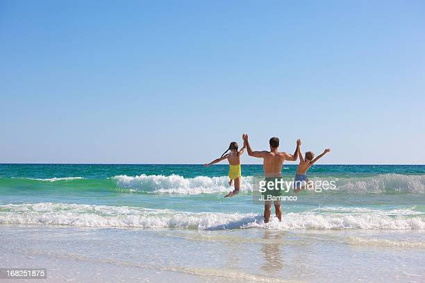 daddy and children at beach - spring break stock pictures, royalty-free photos & images