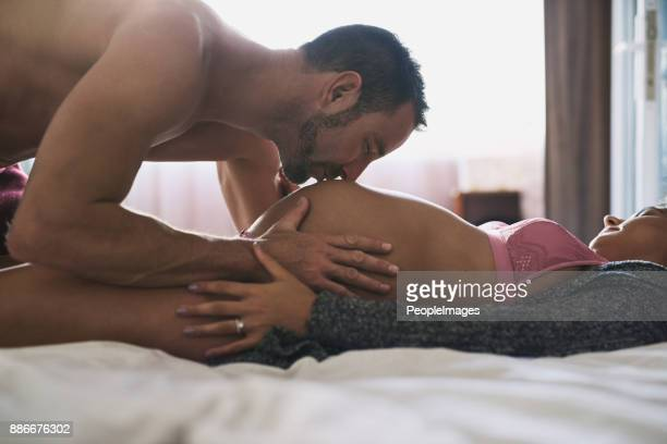 daddy can't wait to meet you - man and woman kissing in bed stock photos and pictures