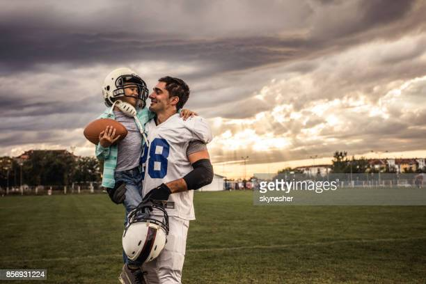 daddy, i want to be american football player just like you! - american football uniform stock pictures, royalty-free photos & images