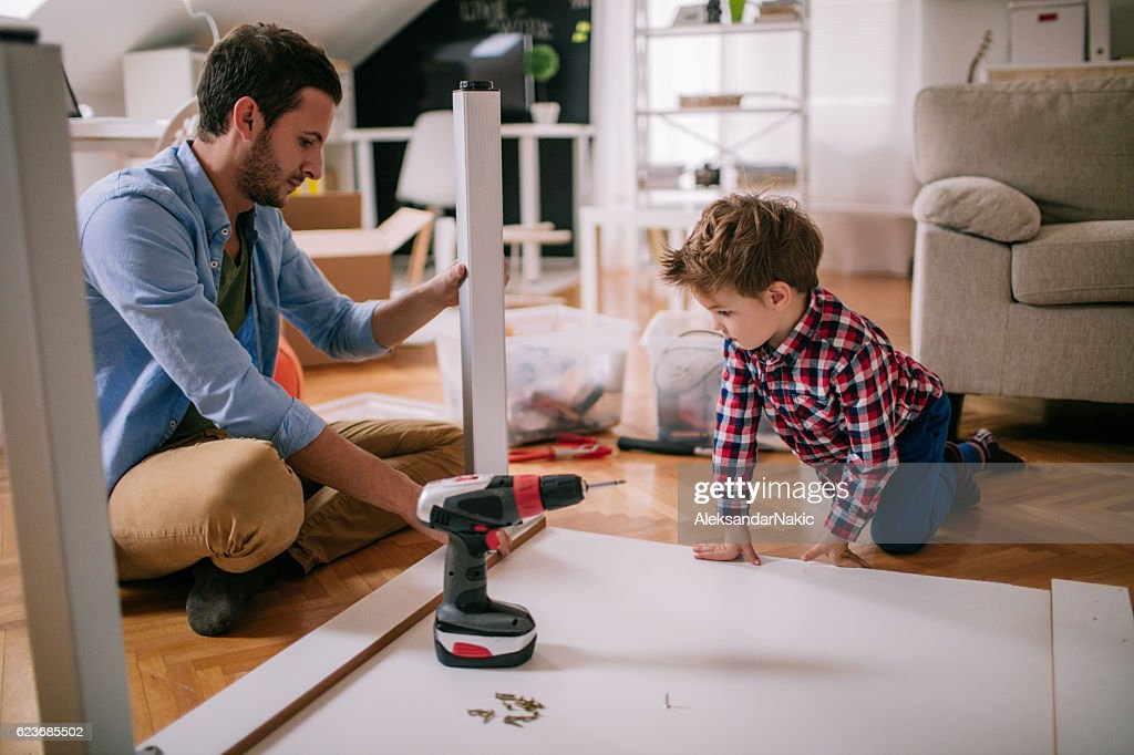 Little boy is trying to assemble the furniture with a little help from his father, in their living room