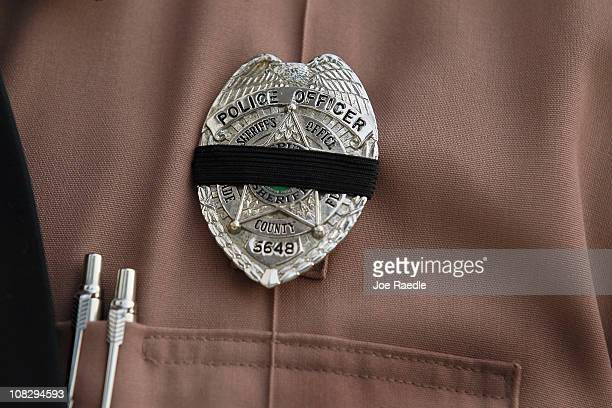 Dade County Sheriff officer wears a black band on his badge as he attends the memorial service of two MiamiDade police officers Amanda Haworth and...