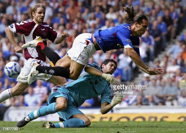 Dado Prso of Rangers is tackled by Craig Gordon of Hearts during the Scottish Premier League match between Rangers and Hearts at Ibrox on August 19...