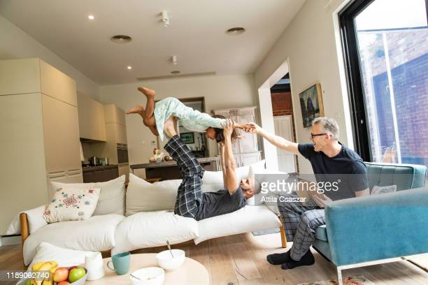 dads and daughter playing on couch - mixed race person stock pictures, royalty-free photos & images