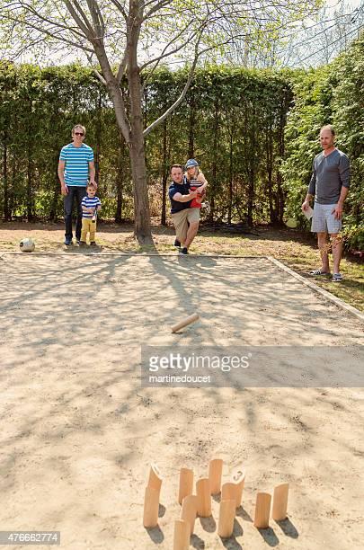 Eltern und kleine Kinder Molkky, Holz Kegeln Spiel im Freien.