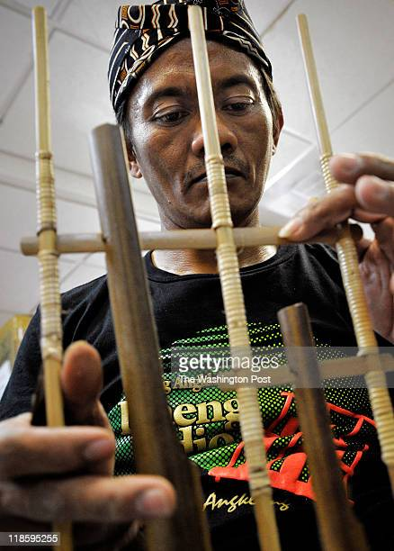 Daeng Udjo maestro of the angklung Indonesian musical instrument changes the pitch on one of them for tomorrow's mass concert on July 2011 in...