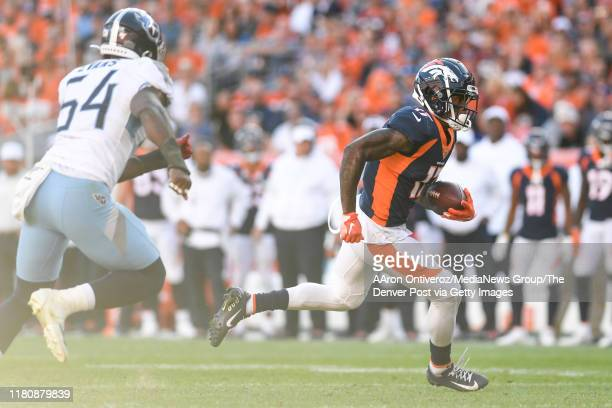 DaeSean Hamilton of the Denver Broncos runs for a first down on a reception from Joe Flacco as Rashaan Evans of the Tennessee Titans pursues during...