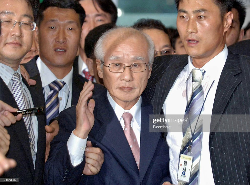 Daewoo Group founder Kim Woo Choong, center, is escorted by Pictures