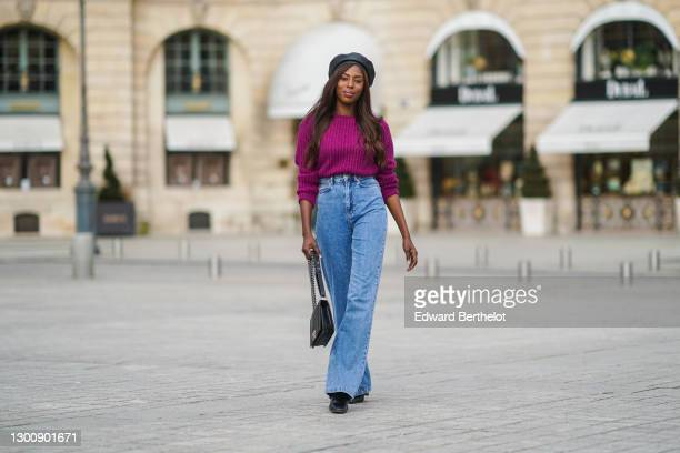 Dafa Traoré aka Poplyve wears a black leather beret hat, a purple wool pullover from Imprévu, a Chanel bag, blue flared denim jeans pants from...
