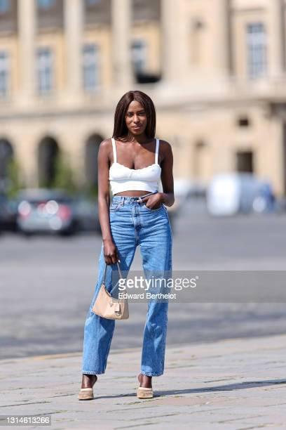 Dafa Traoré @poplyve wears a white cropped ruffle sleeveless tank top, high waist blue denim jeans pants, a beige Prada bag, high heels mesh shoes on...