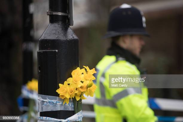 Daffodils are attached to a lamp post as Police continue to guard a police forensics tent in place over a bench at the scene connected to the Sergei...