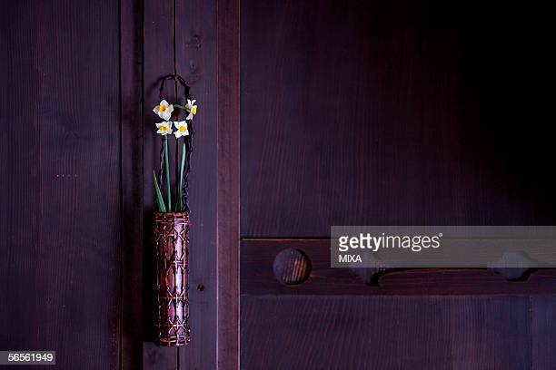 Daffodils in a vase hanging in a house