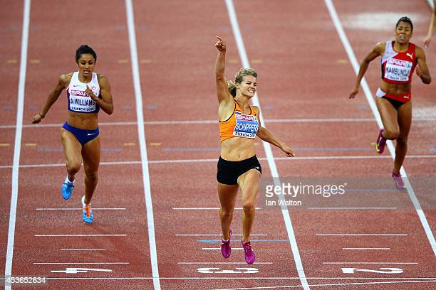 Dafne Schippers of the Netherlands celebrates after winning gold next to silver medalist Jodie Williams of Great Britain and Northern Ireland and...
