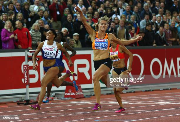 Dafne Schippers of the Netherlands crosses the line to win gold as Ashleigh Nelson of Great Britain and Northern Ireland wins bronze in the Women's...