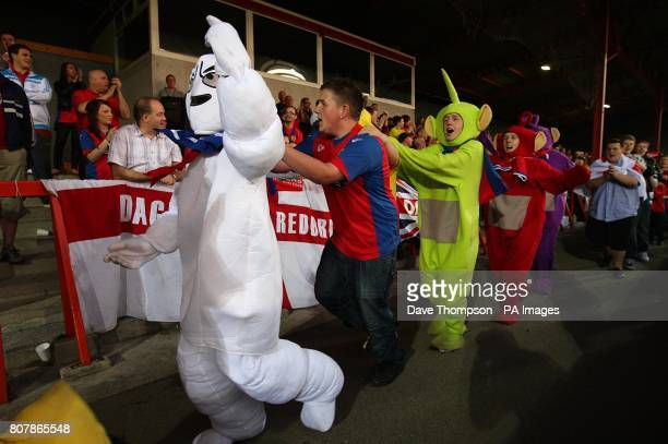 Dagenham and Redbridge fans in fancy dress do a conga around the stadium