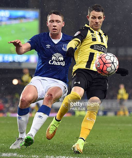 Dagenham and Redbridge's English forward Jamie Cureton vies with Everton's English defender Matthew Pennington during the FA Cup thirdround football...