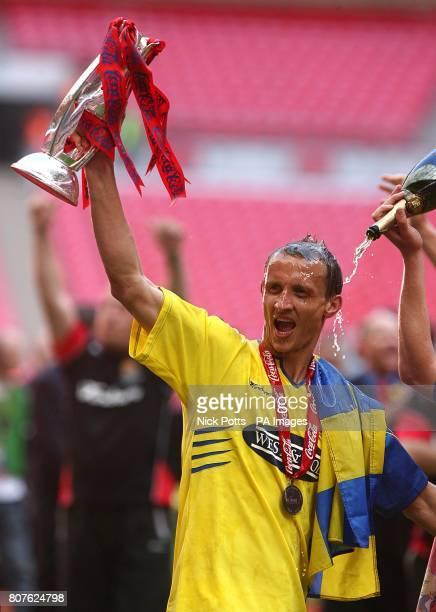 Dagenham and Redbridge's Paul Benson celebrates with the trophy