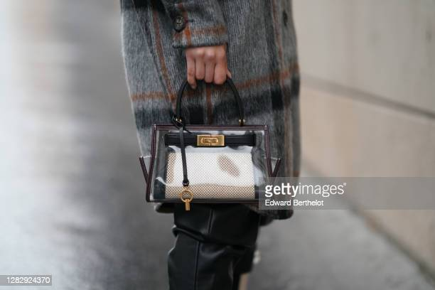 Dagmara Jarzynka wears black leather pants, a gray wool oversized long coat with checked pattern from Copenhagen Muse, a bag from Tory Burch, on...