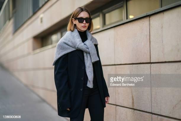 Dagmara Jarzynka wears Celine sunglasses, a gray wool oversized pullover over the shoulders, a black oversized blazer jacket, a black turtleneck top,...