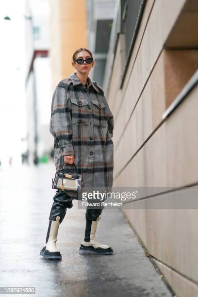 Dagmara Jarzynka wears sunglasses, a gray wool oversized long coat with checked pattern from Copenhagen Muse, a bag from Tory Burch, black and white...