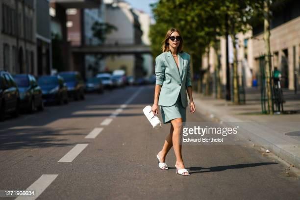 Dagmara Jarzynka wears sunglasses, a pale green oversized blazer jacket/suit from Designers Remix, shorts, a white leather cylinder-shaped long bag,...