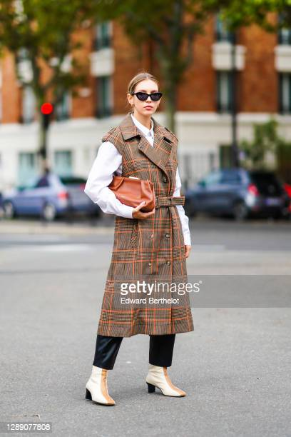 Dagmara Jarzynka wears sunglasses, a white shirt, a brown leather bag, a sleeveless long brown checked trench coat, black pants, brown and white...