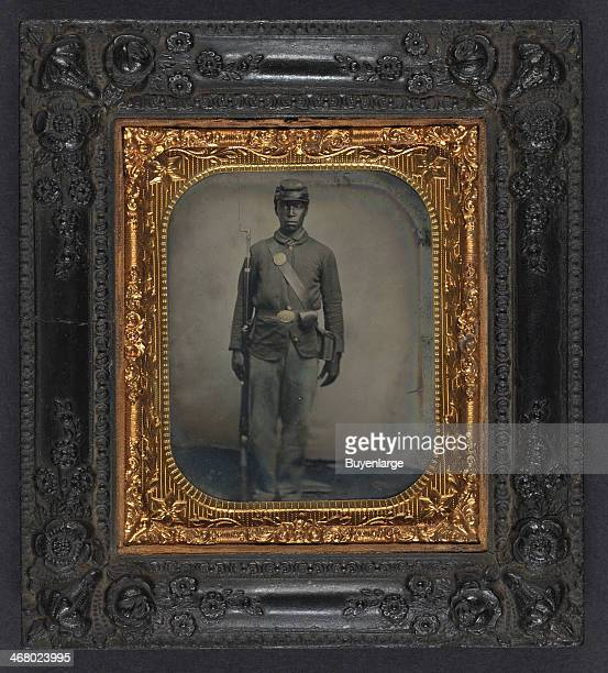 Daguerreotype of an AfricanAmerican soldier in Union uniform with bayoneted musket cap box and cartridge box 1862