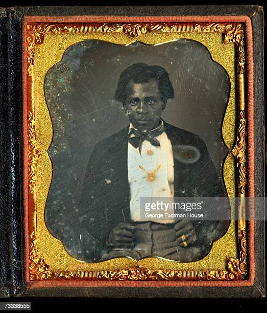 Daguerreotype with applied color frame and details of an unidentified man sitting with his fists on his legs 1850s