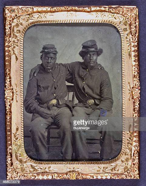 Daguerrotype portrait of two AfricanAmerican Union soldiers in uniform and seated with their arms around each other's shoulders 1863