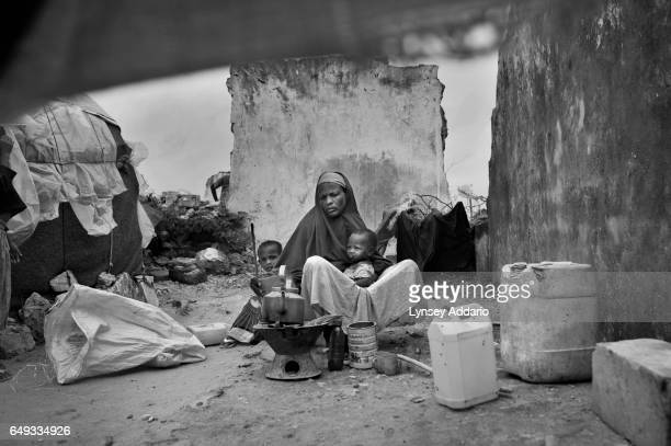Dahaba Ali Taco sits with two of her five children after arriving from Aden Yabal north of Mogadishu to the Badbaado camp for internally displaced...