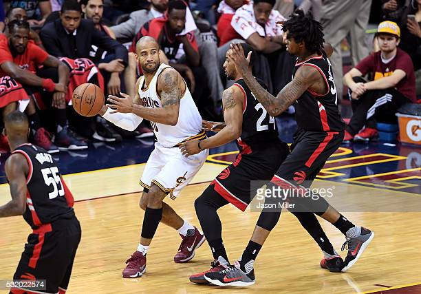 Dahntay Jones of the Cleveland Cavaliers looks to pass in the fourth quarter against Norman Powell and Lucas Nogueira of the Toronto Raptors in game...