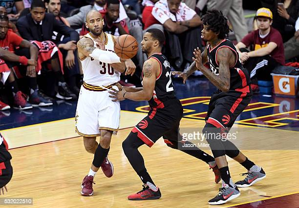 Dahntay Jones of the Cleveland Cavaliers passes in the fourth quarter against Norman Powell and Lucas Nogueira of the Toronto Raptors in game one of...