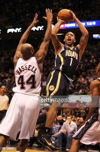 Dahntay Jones of The Indiana Pacers shoots over Trenton Hassell of the New Jersey Nets during their game on November 17 2009 at The Izod Center in...