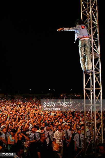 Dai Qin of the 'Thin Man' band from China climbs on a stand to perform at the first 'Green Flag Erdos Grassland Rock Music Festival' near the...