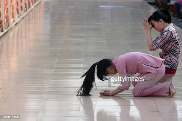 Dai Tong Lam Tu Buddhist Temple Woman praying in front of Buddha Amitabha statues Ba Ria Vietnam