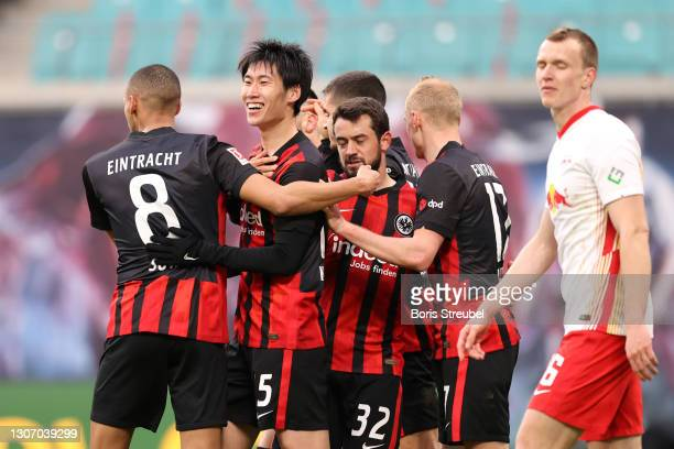 Daichi Kamada of Eintracht Frankfurt celebrates with Djibril Sow and Amin Younes after scoring their side's first goal during the Bundesliga match...