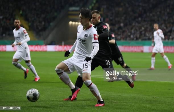 Daichi Kamada of Eintracht Frankfurt is challenged by Maximilian Eggestein of SV Werder Bremen during the DFB Cup quarterfinal match between...