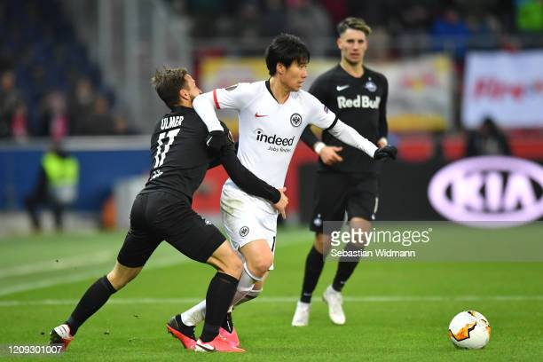 Daichi Kamada of Frankfurt and Andreas Ulmer of Salzburg battle for possession during the UEFA Europa League round of 32 second leg match between RB...
