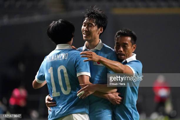 Daichi Kamada of Japan celebrates scoring his side's second goal with his team mates Takumi Minamino and Yuto Nagatomo during the friendly match...
