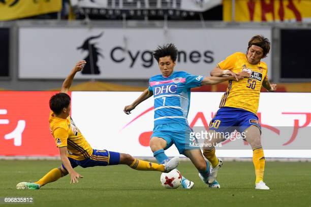 Daichi Kamada of Sagan Tosu controls the ball under pressure of Hirotaka Mita and Tatsuya Masushima of Vegalta Sendai during the JLeague J1 match...