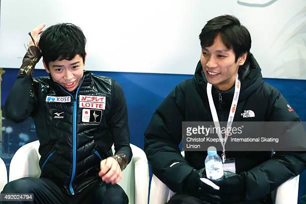 Daichi Miyata of Japan and his coach Naoki Shigematsu smile after the presentation of the junior men free skating of the ISU Junior Grand Prix at Dom...