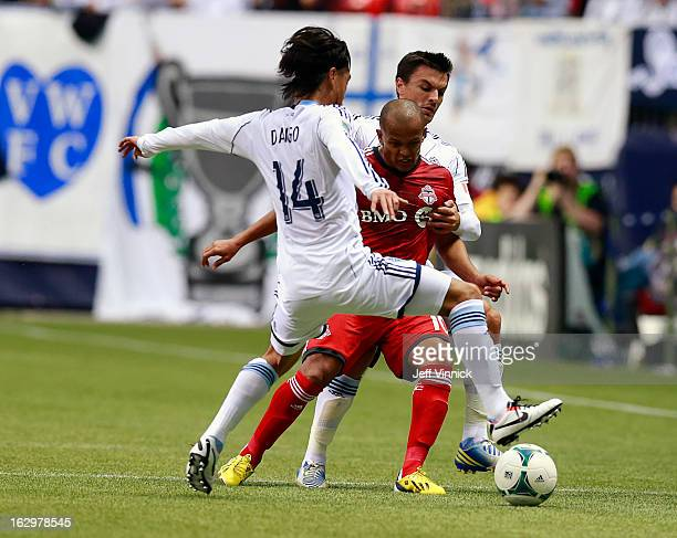 Daigo Kobayashi and Alain Rochet of the Vancouver Whitecaps FC defend against Robert Earnshaw of the Toronto FC during their MLS game at BC Place...