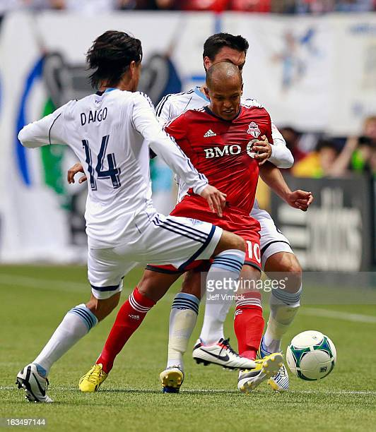 Daigo Kobayashi and Alain Rochet of the Vancouver Whitecaps FC defend against Robert Earnshaw of the Toronto FC during their MLS game March 2 2013 in...