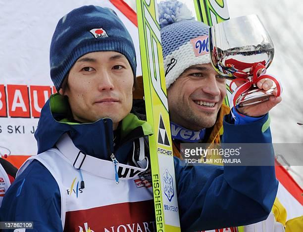 Daiki Ito of Japan raises his winning cup beside Andreas Kofler of Austria on the podium of the FIS World Cup Ski Jumping at the Okurayama Jumping...