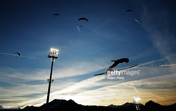 Daiki Ito of Japan soars through the air with paragliders during his practice jump on Day 2 of the 64th Four Hills Tournament on December 29, 2015 in...